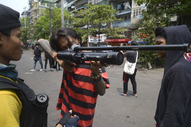 Anti-coup protesters aim with homemade air rifle during a protest in Yangon, Myanmar, Saturday, April 3, 2021. (Photo by AP Photo/Stringer)