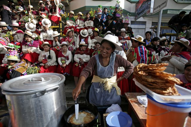 A woman prepares wheat fritters for sale during the Anata Andina (Andean carnival) parade in Oruro, February 12, 2015. (Photo by David Mercado/Reuters)