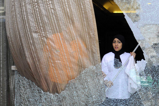A hotel employee cleans smashed glass of the facade of a hotel that was attacked by gunmen, near the pyramids of Giza, Egypt, 07 January 2016. According to reports, a group of men fired fireworks and birdshots towards a hotel near the famous pyramids of Giza, southwest of Cairo, causing damage to the windows of a bus outside the building and the facade of the hotel. No casualties were reported in the attack, while one man was arrested from the scene. (Photo by Nameer Galal/EPA)