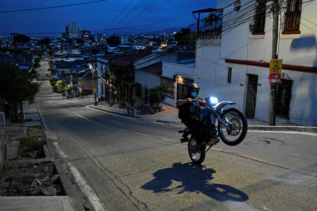 A man rides his motorcycle along an empty street in Cali on April 17, 2021, during a curfew imposed by the government to help curb infections of the novel coronavirus, COVID-19, as weekend partial lockdown takes effect in four Colombian cities. In recent weeks, the Colombian government has imposed, and then tightened, a series of restrictions to stem a third wave of infections that is bringing its health system to the brink of collapse. (Photo by Luis Robayo/AFP Photo)