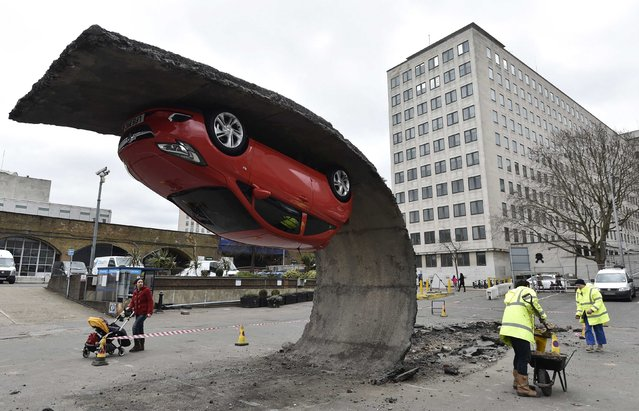 "Pedestrians and workers pass an upside down car art installation in a car park on the South Bank in London, February 19, 2015. British artist Alex Chinneck's illusory piece, entitled ""Pick yourself up and pull yourself together"", and on display in the working car park for a week, sees a Vauxhall car suspended upside down, appearing to be gripping onto a peeled back length of tarmac. (Photo by Toby Melville/Reuters)"