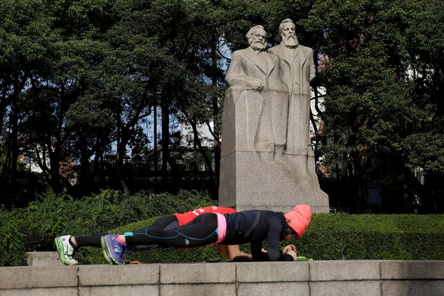 A couple exercises in front of the statue of German philosophers Karl Marx and Friedrich Engels at a park in Shanghai, China December 2, 2016. (Photo by Aly Song/Reuters)