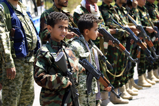 Yemeni children accompanied by their fathers hold weapons during a gathering in Sanaa to show support for the Huthi Shiite movement against the Saudi-led intervention in the capital Sanaa on September 27, 2018. (Photo by Mohammed Huwais/AFP Photo)