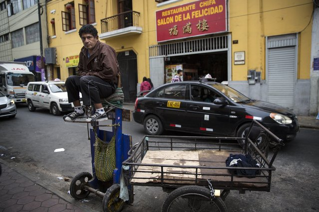A Peruvian porter waits for customers in Lima's Chinatown, Monday, October 1, 2018. Despite accusations facing Lima's leading mayoral candidate Daniel Urresti, the ex-general remains popular with many people who support his hardline stance and yearn for a tough hand against crime in Lima, a city where rich neighborhoods have 10 times as many police officers as poor suburbs. (Photo by Rodrigo Abd/AP Photo)