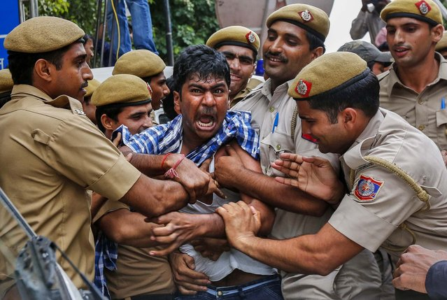 Police detain a supporter of Chandrababu Naidu, chief of Telugu Desam Party as he tries to stop a vehicle from carrying Naidu to a hospital in New Delhi, on Oktober 11, 2013. Naidu has been on a hunger strike since Monday against the creation of Telangana state, according to local media. Two Indian ministers resigned last week over a cabinet decision to create the new state out of the southern Indian state of Andhra Pradesh, a growing hub for Western IT giants. (Photo by Mansi Thapliyal/Reuters)