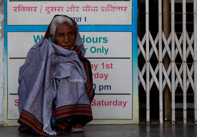 A woman wrapped up in a quilt waits for the bank to open to withdraw her money in Ahmedabad, India, December 2, 2016. (Photo by Amit Dave/Reuters)