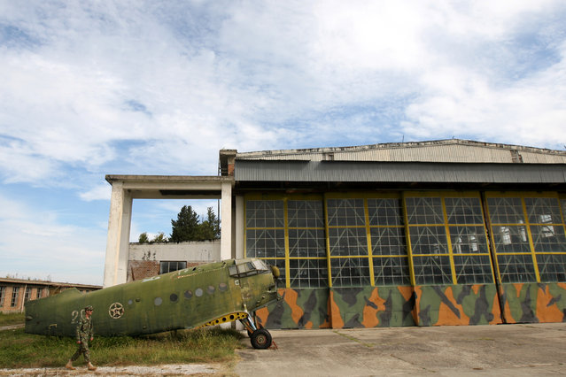 """An Albanian Air Force member walks near an old non-function Airplane (Antonov An-2) in Kucova Air Base in Kucova, Albania on October 3, 2018. Albania retired its 224 Soviet- and Chinese-made MiGs in 2005, and since 2009 NATO neighbors Italy and Greece monitor its airspace. That led to economic decline in and around Kucova, which was called """"Stalin City"""" during the era of Communist rule. (Photo by Florion Goga/Reuters)"""