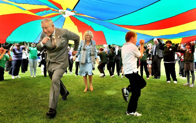 Royal Finalist – John Stillwell. Royal visit to Channel Islands. The Prince of Wales and the Duchess of Cornwall run under a brightly coloured Parachute during a youth rally at Saumarez Park in Guernsey, as they continue their visit to the Channel Islands. (Photo by John Stillwell/Press Association)