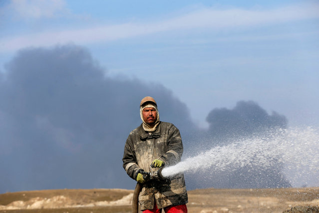 An oil worker uses a hose in front of oilfields burned by Islamic State fighters in Qayyara, south of Mosul, Iraq December 21, 2016. (Photo by Ammar Awad/Reuters)