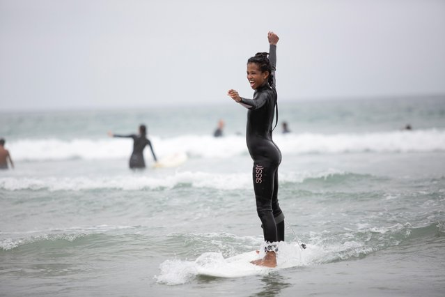 A beginner surfer stands on a surfboard as she attends an event organized by Paddle for Peace and Surfrider to celebrate Juneteenth and International Surf day, at La Jolla shore in San Diego, California, U.S., June 19, 2021. (Photo by Aude Guerrucci/Reuters)