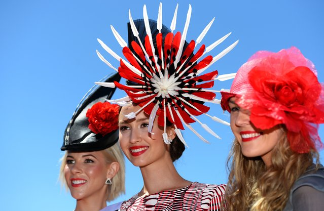 Chloe Moo (C) displays her outfit after winning in the Fashion in the Field competition at the Melbourne Cup in Melbourne on November 5, 2013. (Photo by William West/AFP Photo)