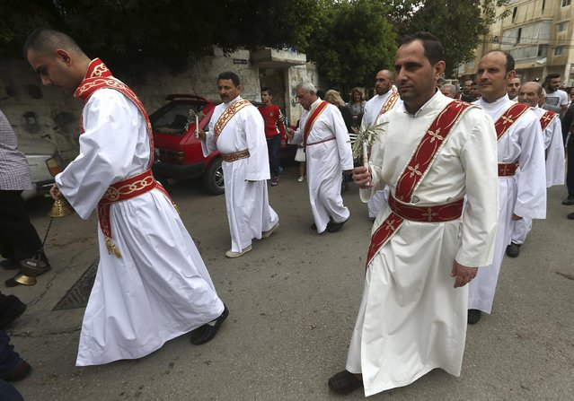Assyrian Christian clergymen lead the traditional Palm Sunday procession as they walk in the street around their church in east of Beirut, Lebanon, Sunday, March 29, 2015. Streams of Christians gathered Sunday to celebrate the path of Jesus Christ's last journey into Jerusalem, when his followers laid palm branches in his path, before his crucifixion. (Photo by Hussein Malla/AP Photo)