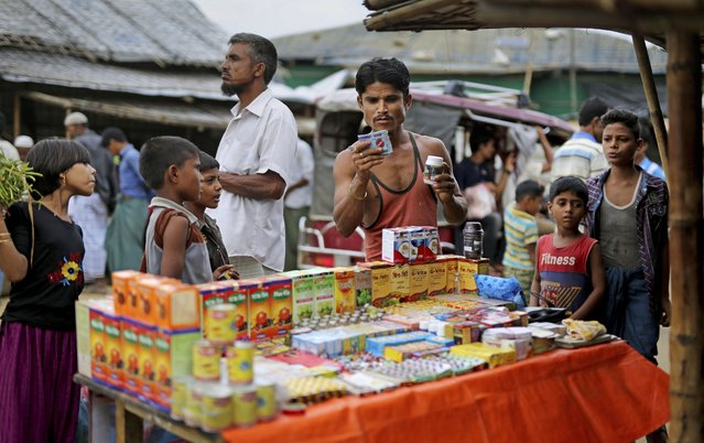 In this photograph taken August 27, 2018, a Rohingya man looks at medicines being sold on the roadside in Balukhali refugee camp, Bangladesh. Faith healers have long been sought out in Rohingya society to treat physical and mental ailments. Their trade has thrived in part because of traditional beliefs and in part because Rohingya have lacked access to modern medical care in Buddhist-majority Myanmar, where they are one of the most persecuted minority groups in the world. (Photo by Altaf Qadri/AP Photo)