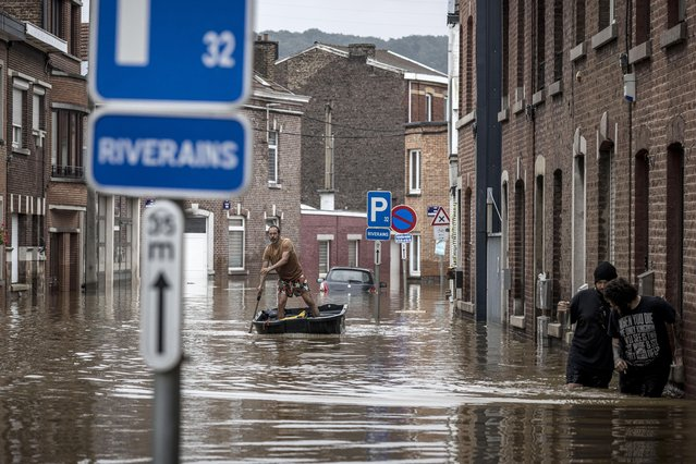 A man rows a boat down a residential street after flooding in Angleur, Province of Liege, Belgium, Friday July 16, 2021. (Photo by Valentin Bianchi/AP Photo)