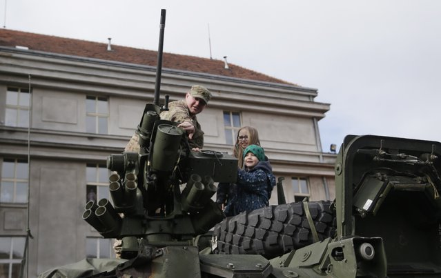 A US army soldier shows a gun mounted on top of a stryker armored vehicle to children during a stop of his convoy in Prague, Czech Republic, Tuesday, March 31, 2015. (Photo by Petr David Josek/AP Photo)