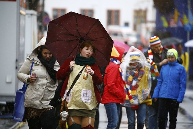 """Carnival revellers battle the wind and rain after the """"Rosenmontag"""" (Rose Monday) parade, the highlight of the annual carnival season, was called-off in Mainz, Germany, February 8, 2016. Many traditional Rose Monday carnival parades were cancelled in the Rhineland due to severe weather warnings. Low-pressure system Ruzica, bringing heavy thunderstorms and high winds is predicted for Monday, according to the weather department. (Photo by Kai Pfaffenbach/Reuters)"""