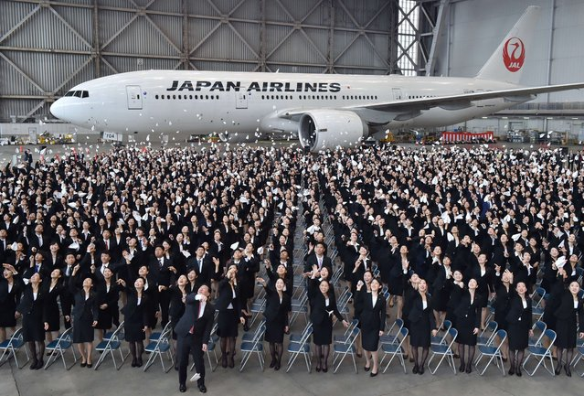 Japan Airlines (JAL) President Yoshiharu Ueki (front, C) and new employees of JAL Group toss carefully folded paper airplanes into the air during the entrance ceremony at a hangar with a Boeing 777 in Tokyo on April 1, 2015. (Photo by Kazuhiro Nogi/AFP Photo)