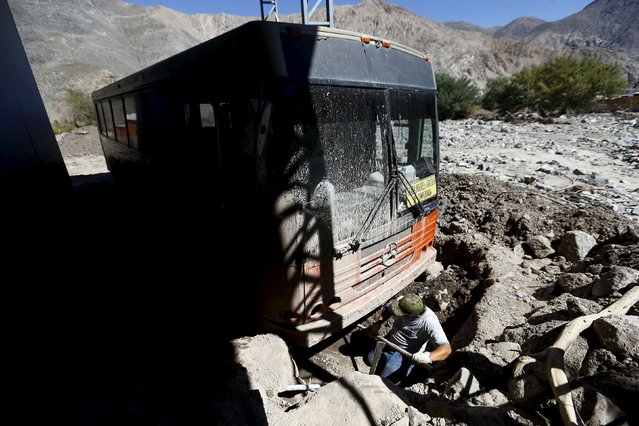 A man digs up his bus at an area which was hit by the floods at Los Loros town, April 7, 2015. (Photo by Ivan Alvarado/Reuters)