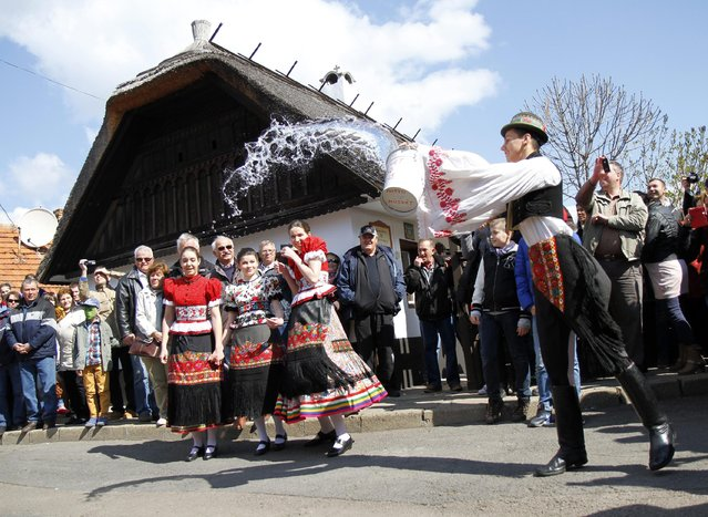 Dressed in folk costume a young man pours water from his bucket on young women in Mezokovesd, 131 kms northeast of Budapest, Hungary, Monday, April 6,2015. According to a several hundred years old tradition of Hungarian villages young men pour water on young women who in exchange present their sprinklers with beautifully colored eggs on Easter Monday. (Photo by Janos Vajda/AP Photo/MTI)