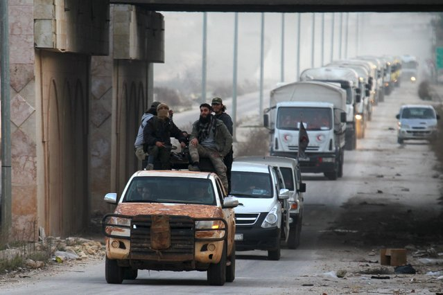 Rebel fighters escort a Syrian Arab Red Crescent aid convoy heading towards the villages of al-Foua and Kefraya in Idlib province, Syria February 17, 2016. (Photo by Ammar Abdullah/Reuters)
