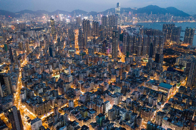 This aerial photo taken on October 23, 2018 shows commercial and residential buildings in Hong Kong at night. (Photo by Dale De La Rey/AFP Photo)