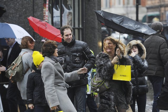 Women shoppers hang on tight to their umbrellas on Oxford Street in London's West End as they battle the rough weather on 23 December 2013. Retailers are hoping the days before Christmas will boost sales during the busiest time of the year. (Photo by Facundo Arrizabalaga/EPA)