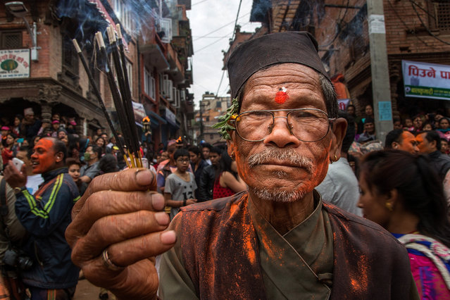 A devotee holds incense sticks while celebrating the Sindoor Jatra Festival on April 15, 2015 in Thimi, Nepal. Sindoor Jatra Festival is celebrated each year in Thimi, on the outskirts of Kathmandu, to welcome the Nepali New Year and celebrate the coming of spring. During the Festival, devotees are smeared with vermillion powder and 30 chariots containing the images of several gods and goddesses are carrying by the devotees around the town, while others sing, dance and play musical instruments. (Photo by Omar Havana/Getty Images)
