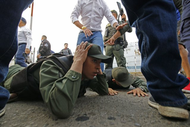 Two Venezuelan soldiers lie on the ground as they are detained by Colombian police after driving into Colombia in an armor car from the Venezuelan side of Simon Bolivar International bridge in Cucuta on February 23, 2019. According to Colombian authorities four soldiers of the Venezuelan guard deserted this Saturday after crossing two border bridges with Colombia, closed by order of the government of Nicol·s Maduro before the announcement of the entry of aid shipments. Three of the soldiers were mobilized in a white tank and knocked down one of the security fences of the Simon BolÌvar Bridge, in the Colombian city of Cucuta, said a Colombian Immigration officer (Photo by Schneyder Mendoza/AFP Photo)