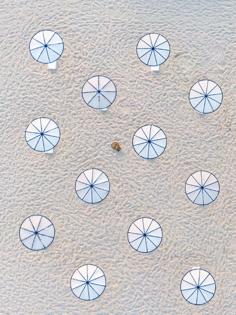 No Stress. Abstract Commended. A lone dog naps on the beach near the parasols. (Photo by Zsolt Dor/Drone Photography Awards 2021)