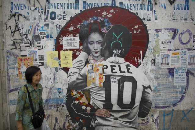 In this December 27, 2018 photo, a woman walks by a mural of Brazilian soccer legend Pele hugging a Geisha in Sao Paulo, Brazil's Asian neighborhood of Liberdade, the area where an influential Japanese-language newspaper ran its last print edition on Jan. 1, 2019. The arrival of the first Japanese immigrants to Brazil was the result of negotiations between Japan and Sao Paulo state, where most Japanese-Brazilians still live. (Photo by Victor R. Caivano/AP Photo)