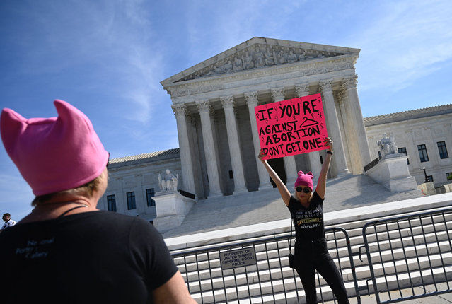"""Protesters hold signs in front of the Supreme Court during the Women's March and Rally for Abortion Justice in Washington, DC, on October 2, 2021. The abortion rights battle took to the streets across the US, with hundreds of demonstrations planned as part of a new """"Women's March"""" aimed at countering an unprecedented conservative offensive to restrict the termination of pregnancies. (Photo by Andrew Caballero-Reynolds/AFP Photo)"""