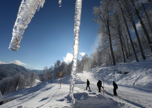 Volunteers walk near the alpine ski course of the Sochi 2014 Winter Olympics, Saturday, February 1, 2014, in Krasnaya Polyana, Russia. (Photo by Luca Bruno/AP Photo)