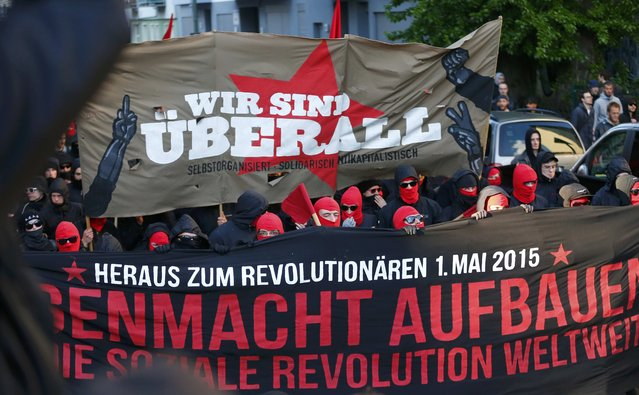 "Masked protestors walk during a May Day march through Berlin's Kreuzberg district, Germany, May 1, 2015. The text over the red star reads ""We are everywhere"". (Photo by Hannibal Hanschke/Reuters)"