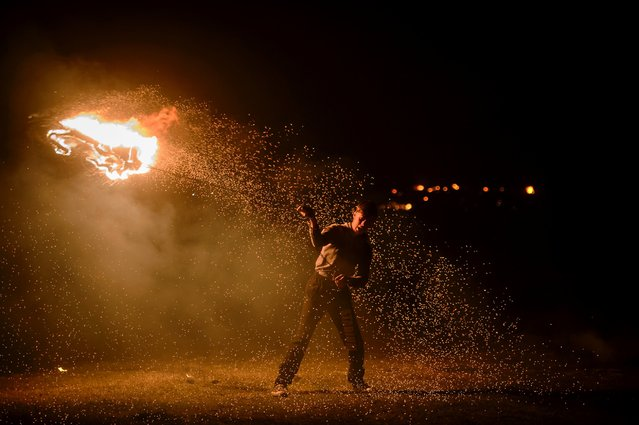 A young man spins a flaming old car tire on a metal chain, during a celebration marking the upcoming Clean Monday, the first day of Great Lent in the Eastern Orthodox Christian church calendar, Sibiu, Romania. (Photo by Andreea Alexandru/AP Photo)