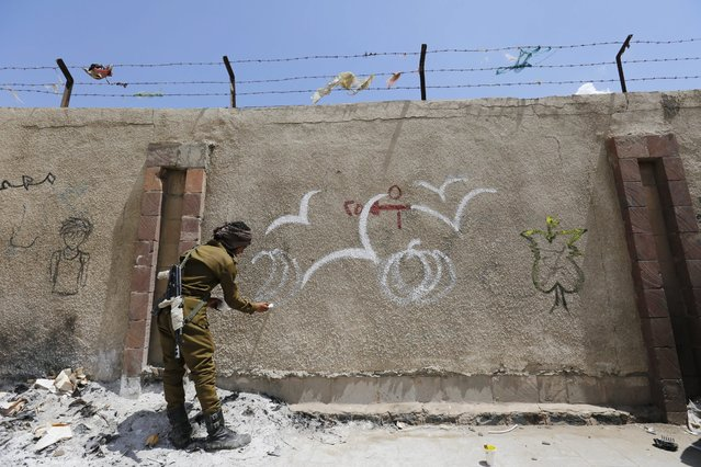 An armed Yemeni soldier paints a graffito in support of peace in the war-affected country, at a wall along a street in Sana'a, Yemen, 16 March 2016. The Saudi-led coalition performs military operations in Yemen since March 2015, targeting areas controlled by the Houthi rebels who overthrew the Saudi-backed Yemeni government. (Photo by Yahya Arhab/EPA)