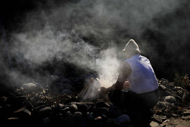 Bathhouse master Ivan Tkach starts a fire to heat up the stones for a sweat lodge at the bathhouse. (Photo by Jae C. Hong/Associated Press)