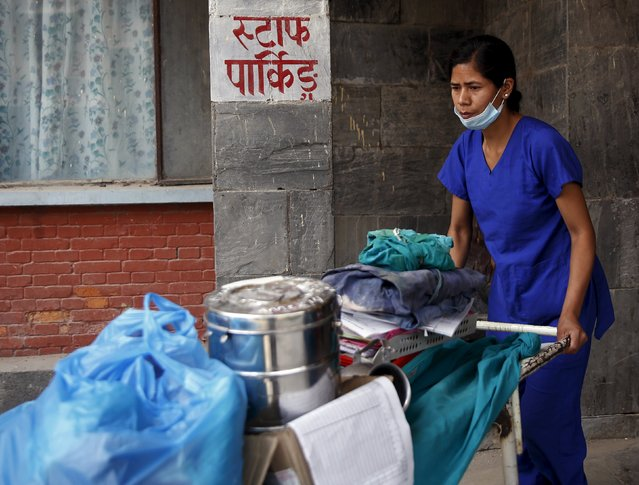 A health worker moves medical supplies out of the maternity hospital which was damaged by the April 25 earthquake and is no longer in use in Kathmandu, Nepal, May 7, 2015. (Photo by Olivia Harris/Reuters)