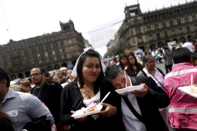 A couple holds a cake as they pose for a photo after a mass wedding ceremony in which 2,016 couples participated, at Zocalo square in Mexico City, Mexico, March 19, 2016. (Photo by Edgard Garrido/Reuters)