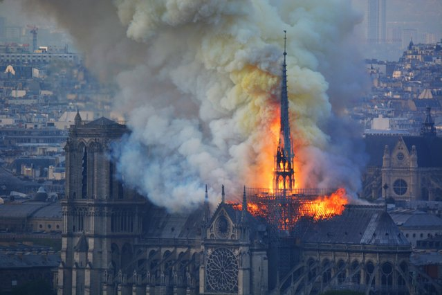 Smoke and flames rise during a fire at the landmark Notre-Dame Cathedral in central Paris on April 15, 2019, potentially involving renovation works being carried out at the site, the fire service said.  (Photo by Hubert Hitier/AFP Photo)