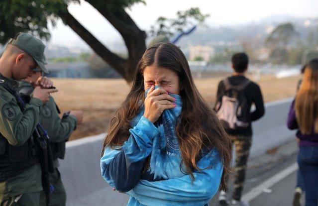 A woman reacts to tear gas near the Generalisimo Francisco de Miranda Airbase in Caracas, Venezuela April 30, 2019. (Photo by Manaure Quintero/Reuters)
