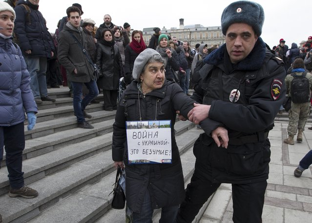 "An elderly woman wearing a sign that reads ""War against Ukraine is madness"" is detained by riot police during an unsanctioned anti-war rally close to the Kremlin at Manezhnaya Square on March 2, 2014 in Moscow, Russia, Dozens of protesters were detained by police on Sunday during a rally against the military intervention in the Ukraine, after the parliament in Moscow gave President Vladimir Putin approval to use Russian military forces in Ukraine. (Photo by Sasha Mordovets/Getty Images)"