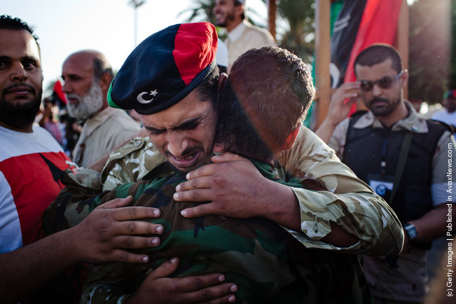 Libyan rebels soldiers embrace as they grieve at Martyr Square formerly known as Green Square, for the Eid Al-Fitr prayer