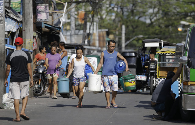 A couple carries empty containers looking for places to collect water in Mandaluyong, metropolitan Manila, Philippines on Thursday, March 14, 2019. Aside from the daily line of residents waiting for water rations from trucks, many businesses like laundry shops, carwash and water-purifying stations in Manila have been affected by a water shortage from the Manila Water Company due to low levels at the La Mesa dam and the onset of El Nino which causes below normal rainfall conditions. (Photo by Aaron Favila/AP Photo)
