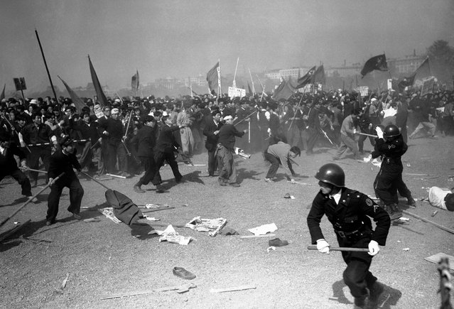 Pro-communist demonstrators stone Japanese policemen at the height of May Day riots in downtown Tokyo on May 1, 1952. Casualties were numerous on both sides as police used tear gas, guns and clubs to beat back the waves of rioters. (Photo by Max Desfor/AP Photo via The Atlantic)