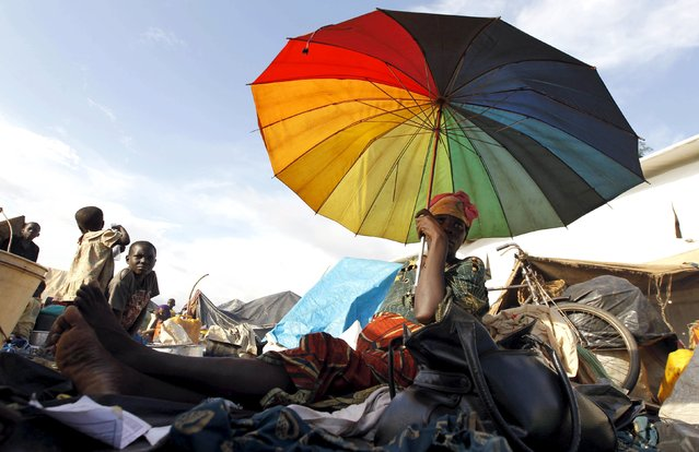 A Burundian refugee holds an umbrella as they gather on the shores of Lake Tanganyika in Kagunga village in Kigoma region in western Tanzania, to wait for MV Liemba to transport them to Kigoma township, May 17, 2015. (Photo by Thomas Mukoya/Reuters)