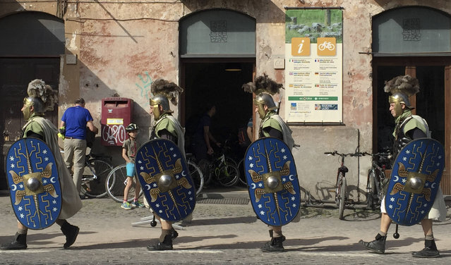 Men dressed in ancient Roman costumes walk in front of a bicycle rental store along the ancient Appian Way, in Rome, Sunday, April 3, 2016. (Photo by Beatrice Larco/AP Photo)