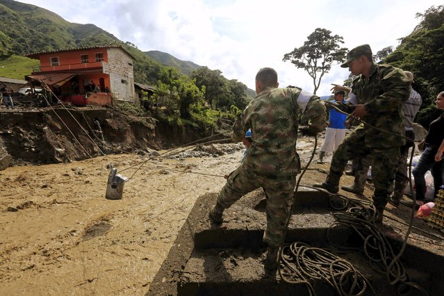 Colombian soldiers help to collect supplies for residents after a landslide sent mud and water crashing onto homes close to the municipality of Salgar in Antioquia department, Colombia May 19, 2015. (Photo by Jose Miguel Gomez/Reuters)