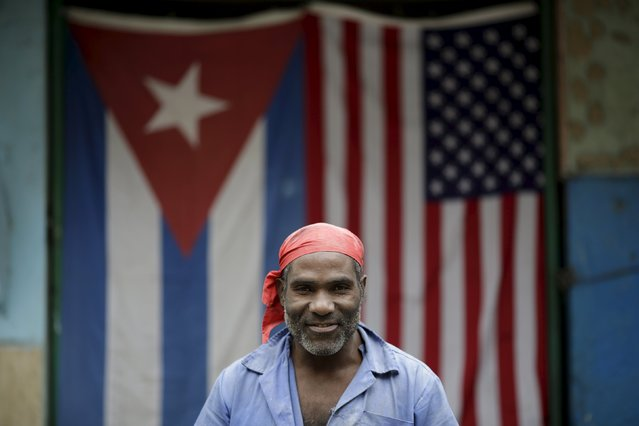 "Manuel, 52, a bricklayer, poses for a photograph in front of the Cuban and U.S. flags in Havana, March 25, 2016. Regarding Obama's historic visit to the island, Manuel said ""I hope with this visit there will be a little more survival"". (Photo by Ueslei Marcelino/Reuters)"
