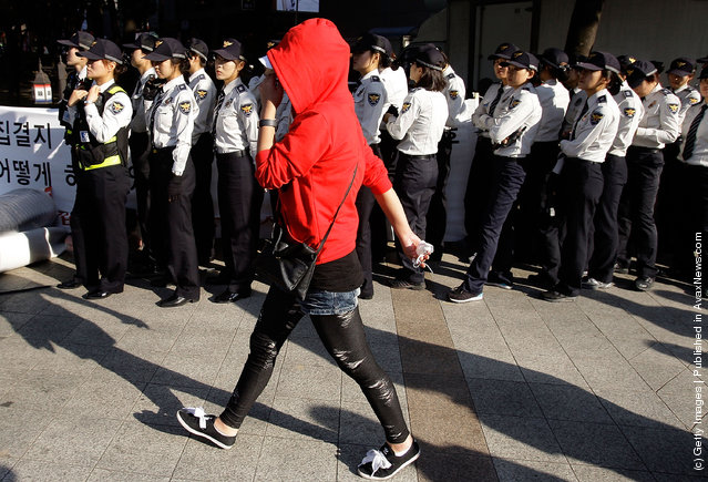 A South Korean prostitute walks in front of police