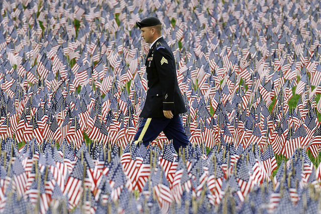 A soldier walks on a path through the Massachusetts Military Heroes Fund flag garden on Boston Common in Boston, ahead of Memorial Day, Thursday, May 21 2015. Each of the approximately 37,000 flags represents a Massachusetts military member who died in service from the Revolutionary War to the present. (Photo by Michael Dwyer/AP Photo)